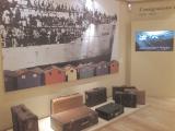 Viaggio (Innocente, 1998, fotografia su tela) e valigie di cartone